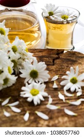 Herbal chamomile tea in cup and glass teapot with fresh chamomile herbs on vintage wooden table background