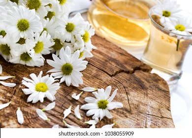 Herbal chamomile tea in a glass cup and glass teapot with fresh chamomile herbs on vintage wooden table background