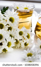 Herbal chamomile tea in a glass cup and glass teapot with fresh chamomile herbs