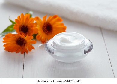 Herbal cosmetic acne cream with calendula vitamin natural organic moisturizer cleansing product with towel. Dermatology hygienic anti aging, wrinkle, blemish, pimple, blackhead clear treatment