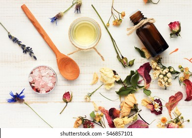 Herbal cosmetic ingredients top view wooden background. Mix of dried holistic flowers scattered, salt, massage herb-infused oil, aroma dropper bottle, spoon