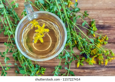 Herbal decoction of medicinal herb Hypericum. Cup of herbal tea from St. John's wort plant on wooden board table, top view