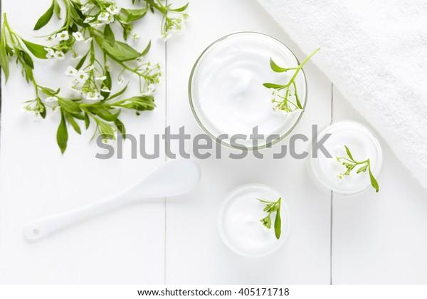 白い背景にガラスのびんに花皮製品を入れたハーブ皮膚科の衛生クリーム