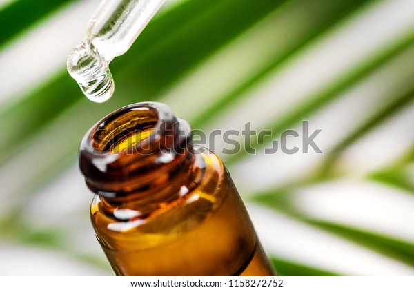 herbal essence. alternative medicine. essential oil dropping from pipette to the bottle
