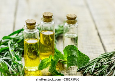 herbal extract in glass bottles, mint and rosemary for spa on wooden table background