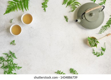 Herbal or Green Tea on white background, top view, copy space. Teapot and teacups with wild plant leaves, natural herbal tea composition.