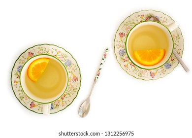 Herbal green tea with slice of orange in pretty springtime teacups.  Isolated on white in flat lay composition.
