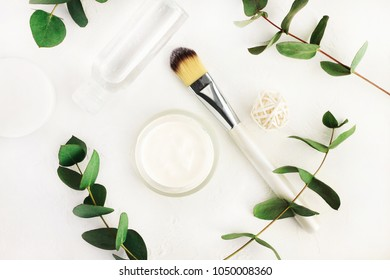 Herbal healing skincare. Jar of cosmetic moisturizer and facial tonic bottle with fresh eucalyptus branches. Simple white and green colors, top view lay on table preparing spa background