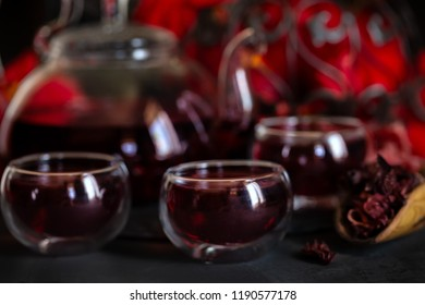 Herbal hibiscus tea carcade with red hibiscus flowers. Dark mood photo.