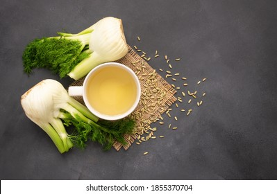 Herbal infusion fennel tea in glass cup or mug with dried fennel seeds and fennel bulbs. Alternative medicine background concept (Foeniculum vulgare)