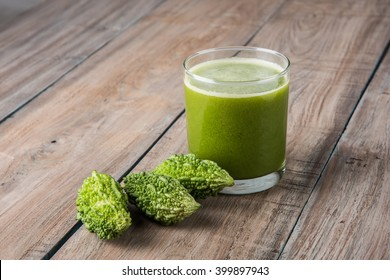 Herbal juice of Bitter gourd or Karela is the best natural medicine for diabetes. Whole green bitter melons and Glass full of Juice kept over colourful or wooden background. Selective focus