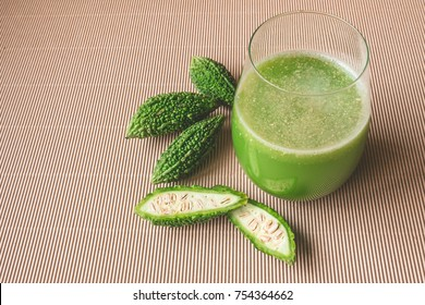 Herbal juice with bitter melon or bitter gourd on wooden background.