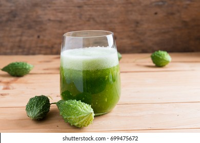 Herbal juice of green momodica , Balsam apple, Balsam pear, Bitter cucumber , Bitter gourd , Stuffed bitter gourd, karela in a glass with sliced vegetables, karela juice or bitter gourd juice