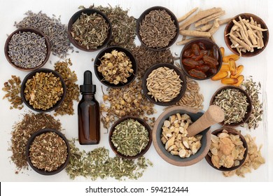 Herbal medicine for anxiety disorders in wooden bowls with mortar and pestle and essential oil bottle on distressed white wood background.
