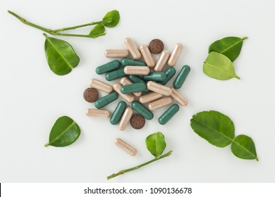 Herbal medicine in capsules with kaffir lime leaf on white background top view