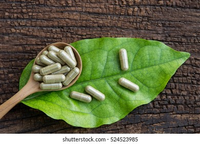 Herbal medicine in capsules on green herb leaf