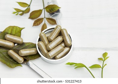 Herbal medicine in capsules on plastic bowl with white table