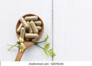 Herbal medicine in capsules on wooden spoon with white table for healthy lifestyle and healthcare  living concept