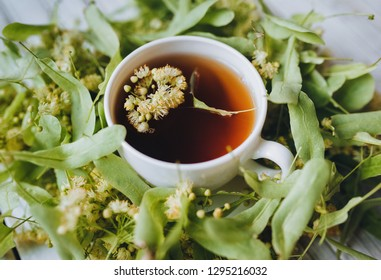 Herbal medicine concept. White cup and dish of linden tea on linden blossom background. Rustic. Top view.