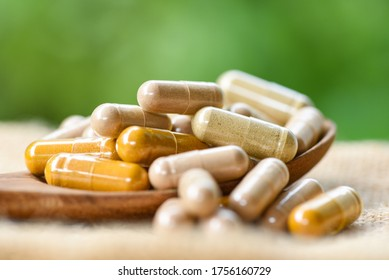 Herbal medicine extract from nature Non-toxic drug organic product on wooden spoon and nature green background / Herbal capsules from herbs healthy lifestyle