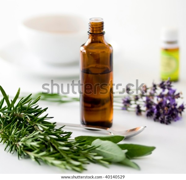 Herbal medicine with herbs and a cup of tea on table. Isolated white background. Studio shot.