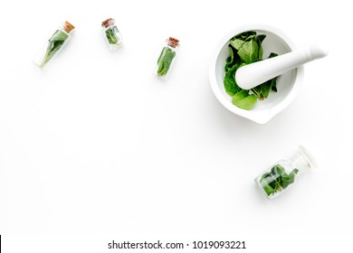 Herbal medicine. Herbs in mortar bowl and in small bottles on white background top view copy space
