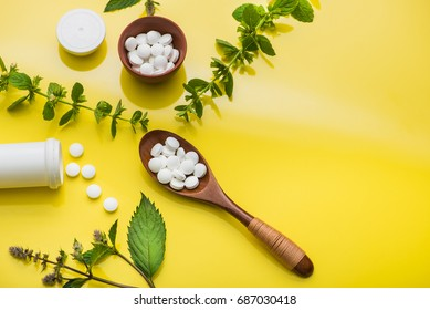 Herbal medicine pills with leaf and bottle on yellow background. top view