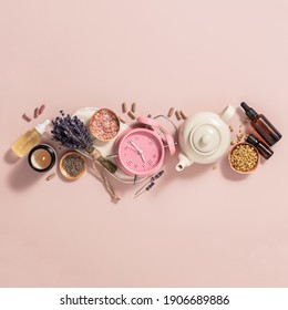 Herbal medicine for treat depression and insomnia concept. Alarm clock, medicine herbs, capsules, camomile tea and aromatherapy oil on pink background, flat lay