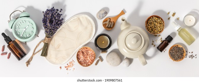 Herbal medicine for treat depression and insomnia concept. Alarm clock, medicine herbs, capsules, camomile tea and aromatherapy oil on white background, flat lay