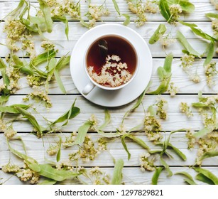 Herbal medicine. White cup of linden tea on linden blossom background. Top view. Treatment of cold and flu concept.