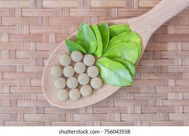 Herbal Medicines. green herbs with healthy medical plant. Green leaf, alternative drug in wooden spoon on wooden background
