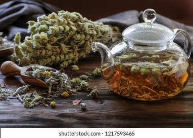Herbal mixture tea leaves tea in the teapot on wooden background, herbal tea concept.
