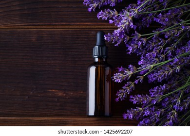 Herbal oil and lavender flowers on wooden background - beauty treatment