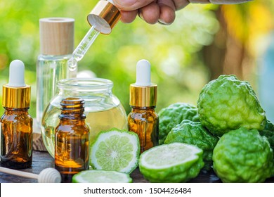 Herbal organic essential oil from bergamot fruit in glass bottles on wooden table with nature blurry background