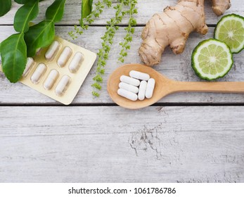 herbal pills in wooden spoon with ginger root, Kaffir lime fruit and basil flower on wood background with copy space. Above view.