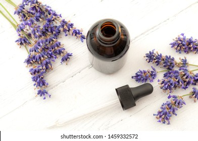 Herbal remedies, holistic health care and alternative medicine concept theme with pipette or glass dropper in brown bottle of tincture surrounded by fresh lavender flowers on white wooden rustic table