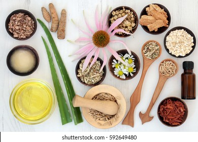 Herbal skincare healing ingredients to soothe psoriasis and eczema on distressed white wood background.