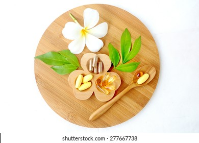 Herbal supplements and vitamins  on wooden tray, decorated with white flowers and green leafs background as white cotton cloth