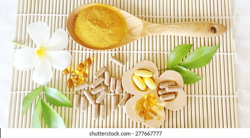 Herbal supplements and vitamins  on wooden trayand dry powder herbal inwooden spoon, decorated with white flowers and green leafsThe backdrop is the bamboo blinds