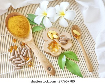 Herbal supplements and vitamins  on wooden tray and wooden spoon, decorated with white flowers and green leafs background as bamboo blinds white cotton cloth
