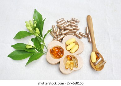 Herbal supplements and vitamins  on wooden tray and wooden spoon, decorated with white flowers and green leafs background as white cotton cloth