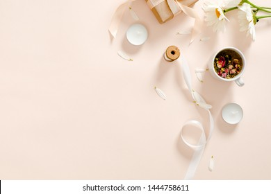 Herbal tea, candles, ribbon, gift box, chamomile flower on pastel pink background. Minimal flat lay style composition, top view, overhead.