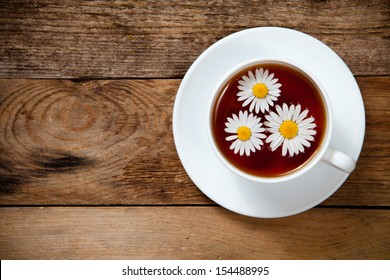 herbal tea with chamomile on old wooden table. Top view. With place for text.