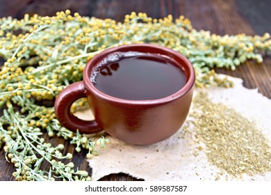 Herbal tea in a clay cup, twigs gray sagebrush, wormwood dried on rough paper on a dark wooden board