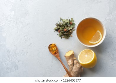 Herbal tea for colds and flu. Lemon, ginger and herbs on concrete background with copy space. Top view.