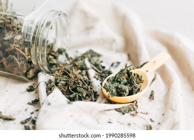 herbal tea. dried nettle leaves. Herbal medicine. wooden spoon with dried nettle leaves near a glass jar with dry nettles on a light background.