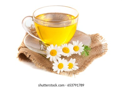 Herbal tea with fresh chamomile flowers on sackcloth isolated on white background