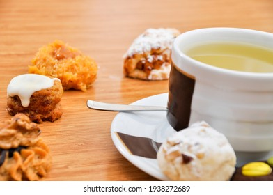 Herbal tea and fresh cookies in white cup on bamboo wooden table