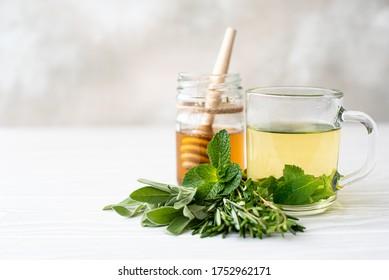 herbal tea with fresh mint, thyme, sage in glass mug