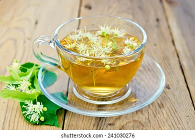 Herbal tea in a glass cup, fresh linden flowers on a wooden boards background